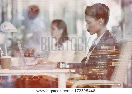Focused businesswoman with colleague working on laptop in office