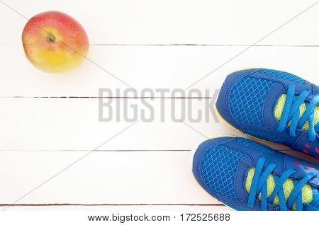 Sneakers and apple on white wooden background. Sport equipment. Selective focus