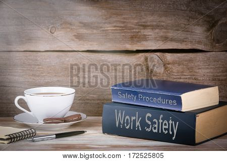 Work Safety and Safety Procedures. Stack of books on wooden desk.