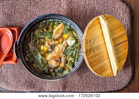 Traditional japanese miso soup in a black bowl and wooden cap, with tofu cheese, mushrooms and seaweed, restaurant table, top view