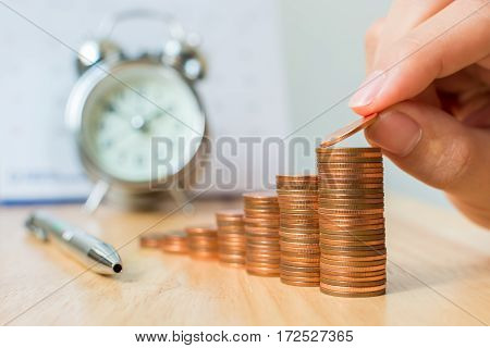 Concept business finance investment save money. Coins stack on wood table with blurred calendar and alarm clock