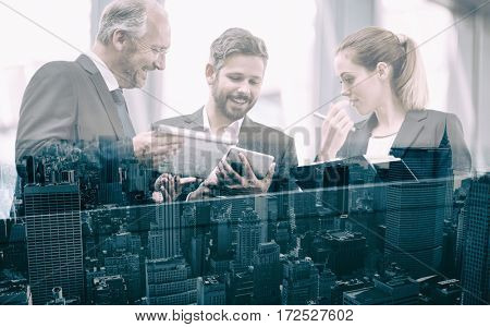 Businesspeople discussing while looking at digital tablet in office