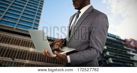 Midsection of businessman using laptop against building against cloudy sky