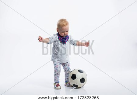 Cute little girl playing with soccer ball. Studio shot on white background.