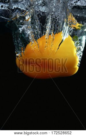 Fresh yellow paprika splash in water on black background