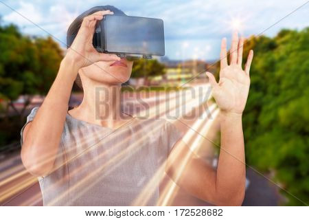 Young woman wearing virtual video glasses against light trails on city street