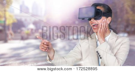 Excited businesswoman pointing while wearing virtual video glasses against blurred new york street