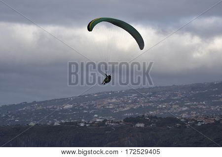 Glider make a turn with clouds in background and the town Puerto de la Crus Tenerife Spain underneath.
