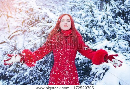 Portrait of a young woman with red hair in winter time with snow