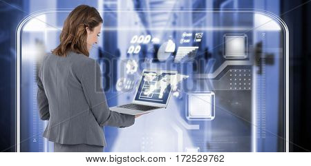 Rear view of businesswoman using laptop against image of data storage 3d