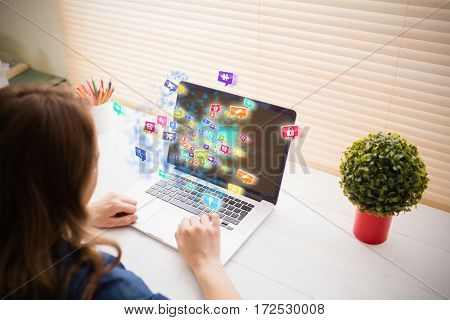 Colourful computer applications against businesswoman using her laptop