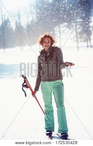 Red-haired young woman has fun with cross-country skiing in the Alps and throws with snow on your winter holiday.