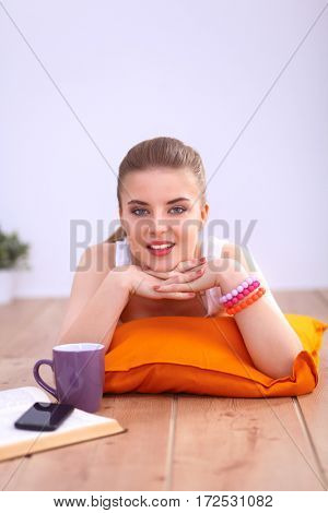 Smiling young woman lying on a white floor with pillow