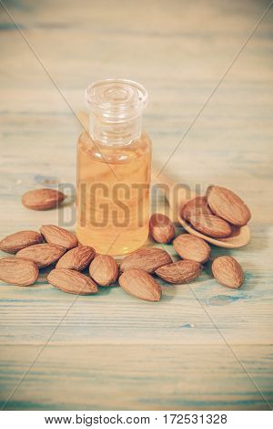 Almonds on wood and yelow oil bottle