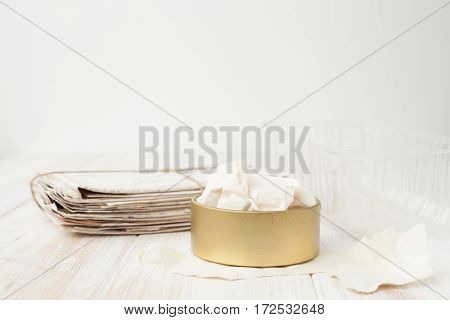 A Bunch Of Old Letters, Torn Paper, Plastic Container, Iron Pot On White Wooden Background