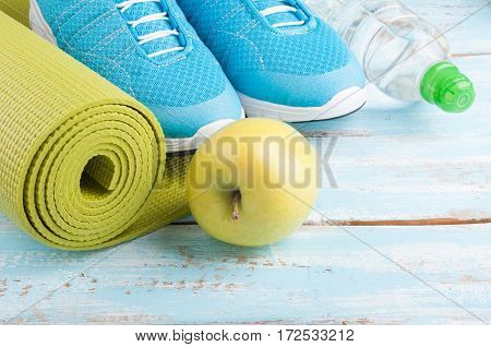 Yoga mat sport shoes apple bottle of water on blue wooden background. Concept healthy lifestyle healthy food sport and diet. Sport equipment. Selective focus