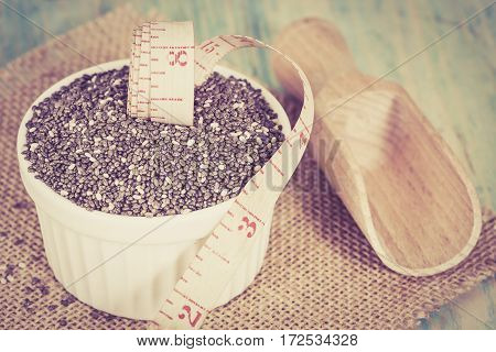 Chia seeds in bowl with measuring tape.