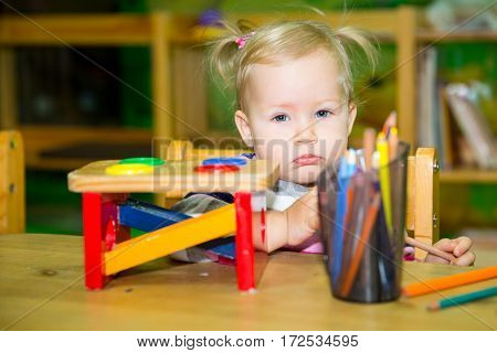 Adorable child girl playing with educational toys in nursery room. Kid in kindergarten in Montessori preschool class.