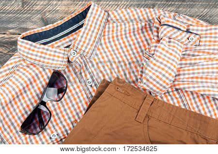Men's casual clothes shirt pants jeans and sunglasses on wooden background. Men's casual or hipster outfits. Top view