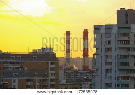 Sunset or sunrise over the city. The orange light. Pipe smoke. Nuclear power plant heating plant