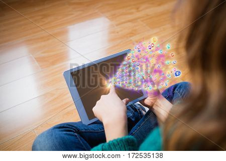 Colourful computer applications against woman looking at tablet