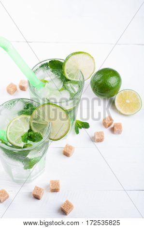 Mojito lime cocktail in bar on wooden backgroung with copy space. Ingredients for making mojito. Summer refreshing drink