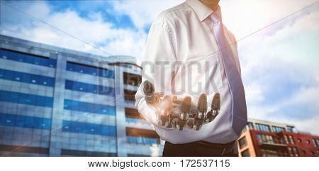 Midsection of businessman with robotic hand against modern buildings against sky 3d