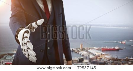 Businessman with robotic hand approaching for handshake against view of city and harbor 3d