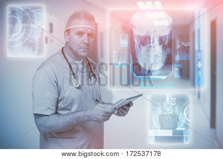 Digitally generated image of human skull against male surgeon holding digital tablet 3d