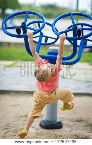 Boy doing exercises on a playground