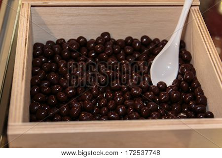 Chocolate Sugared Almonds In Wooden Box With White Spoon