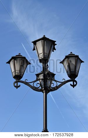 Decorative street lamp. Plane flying in the blue sky.