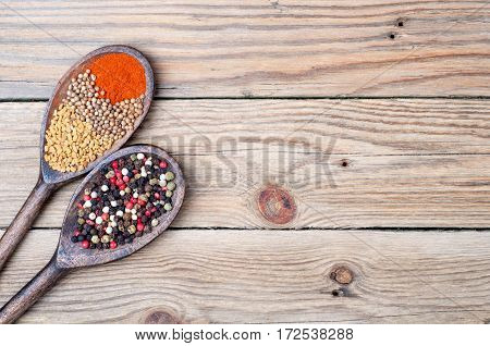Food background with spices in spoons. Paprika pepper fenugreek coriander on old wooden table. Copy space. Top view