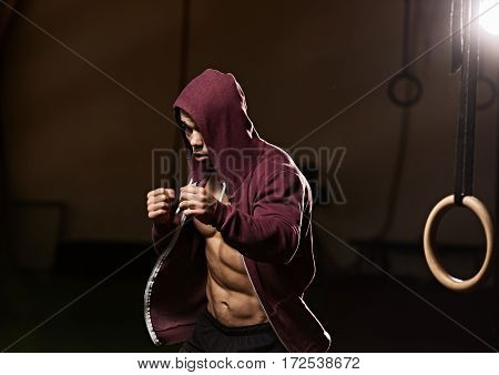 Portrait of strong muscular young boxer training in gym