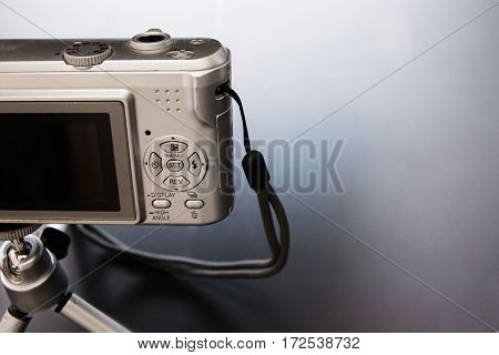 Silver compact digital photo camera. Back view.