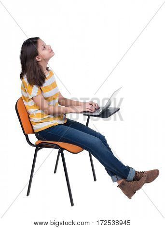 Side view of  woman sitting on a chair to study with a laptop. Isolated  over white background
