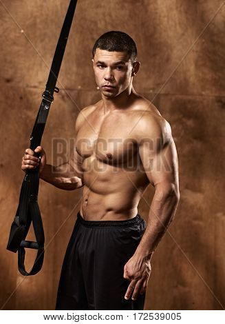 Young muscular athlete doing suspension rope exercise