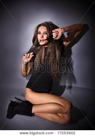Young Slim Glamour Lady With Long Hairs Dressed In Black Combi Dress Sitting On The Floor, Dark Key