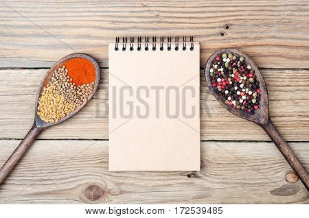 Food background with spices in spoons and open blank notebook with copy space. Paprika pepper fenugreek coriander on old wooden table. Top view