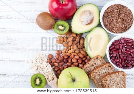Healthy fat sources and healthy food that is useful for heart on wooden background with copy space. Diet and healthy lifestyle concept. Vegetarian food. Top view
