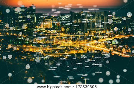 Blue circular shape computer icons against high angle view of illuminated cityscape