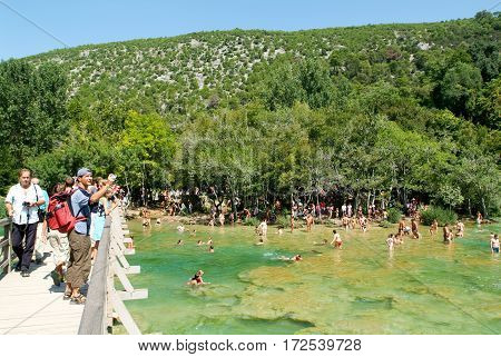 Tourists Walking And Swimming At The Krka National Park