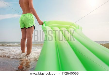 Boy stands on sea surf line with swimming air mattress