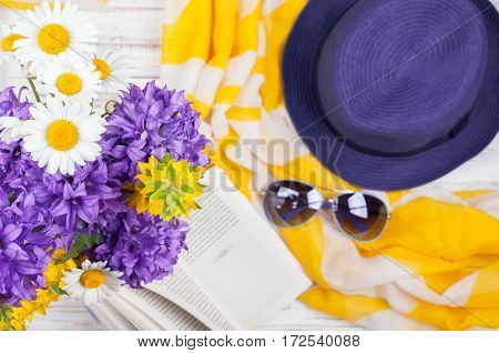 Summer background with flowers book and womans casual accessories - neckerchief hat and sunglasses. Summer rest concept. Top view