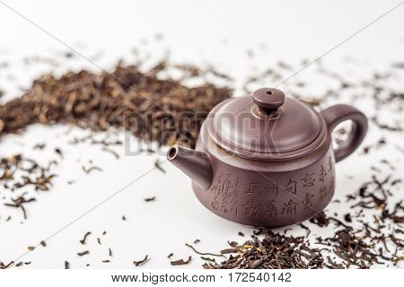 Yixing teapot and black Chinese tea leaves on a white background