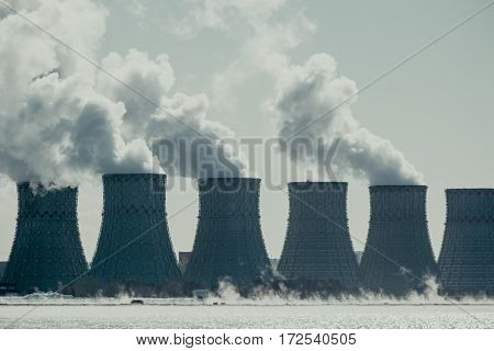 Cooling towers of NPP or Nuclear Power Plant with thick smoke. Dark toned image. Ecological disaster concept