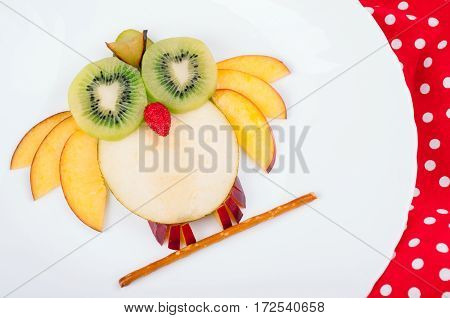 Funny fruits owl or bird for kids breakfast on wooden background. Healthy snacks. Top view