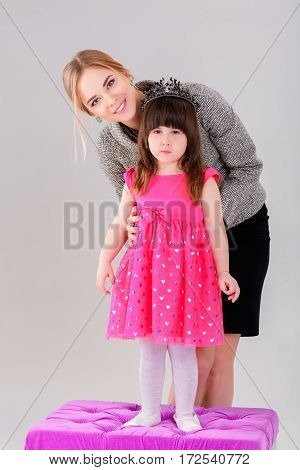 beautiful little girl in pink Princess dress with a crown and beautiful mother hugging on a gray background.