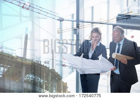 Crane and building construction site against business colleagues discussing with blueprint in corridor