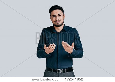 Feeling uncertain. Confused young man shrugging shoulders and making face while standing against grey background